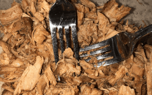 Mixing spices into shredded chicken