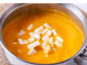 Simmering pumpkin soup with cream cheese cubes